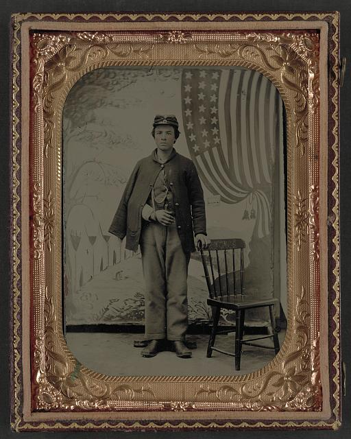 [Unidentified soldier in uniform with arm in sling in front of painted backdrop showing military camp and American flag]