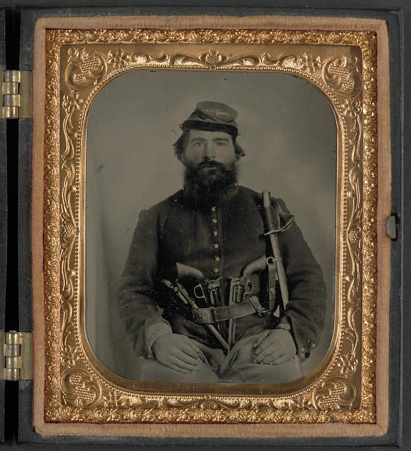 [A. J. Blue, cavalry soldier in Union shell jacket and bummer cap with three Remington revolvers in his belt, holding a sword]