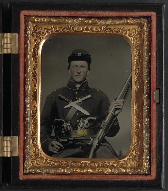[Unidentified soldier in Union uniform with three Remington revolvers, two Bowie knives, and a Springfield rifle musket]