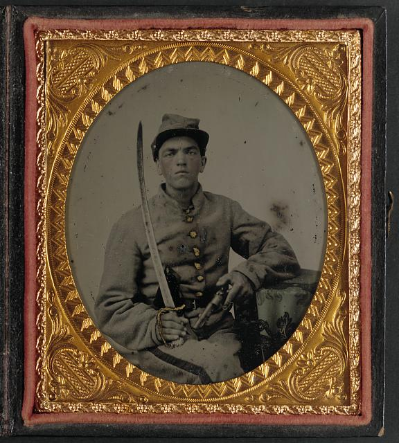 [Unidentified soldier in Confederate uniform holding saber and revolver]