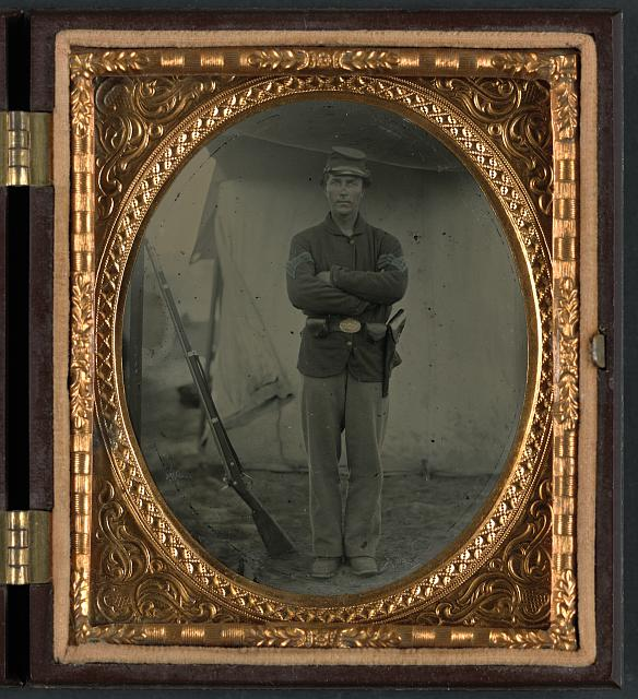 [Unidentified soldier in infantry sergeant uniform with holster and musket in front of tent]