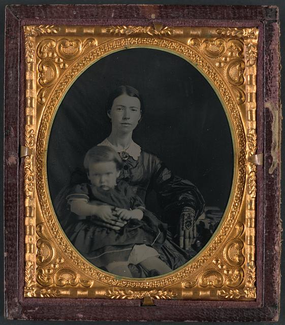 [Unidentified soldier in Confederate uniform in front of painted backdrop showing view from porch; unidentified woman with small child on her lap]