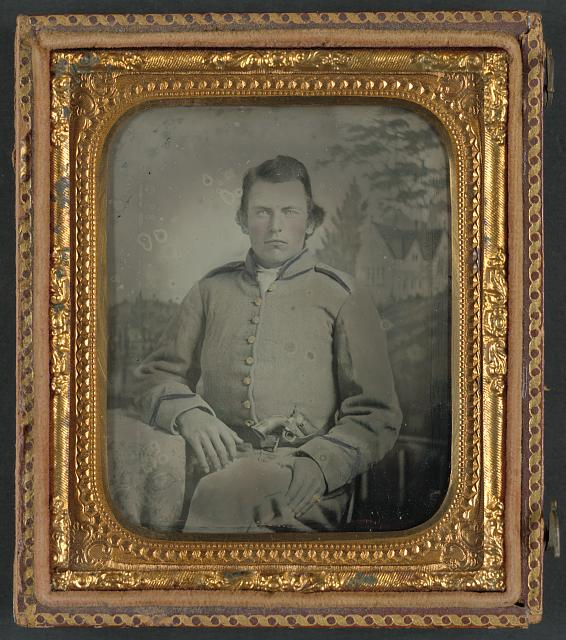 [Lewis Hicks of Company H, 53rd North Carolina Infantry Regiment with pistol in front of painted backdrop showing a gabled house]