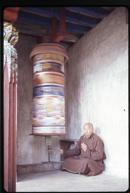 Lama turning prayer wheel activating prayers