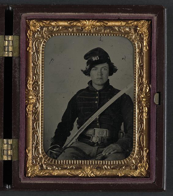 [Unidentified soldier in Union musician uniform and two belts with cavalry saber]