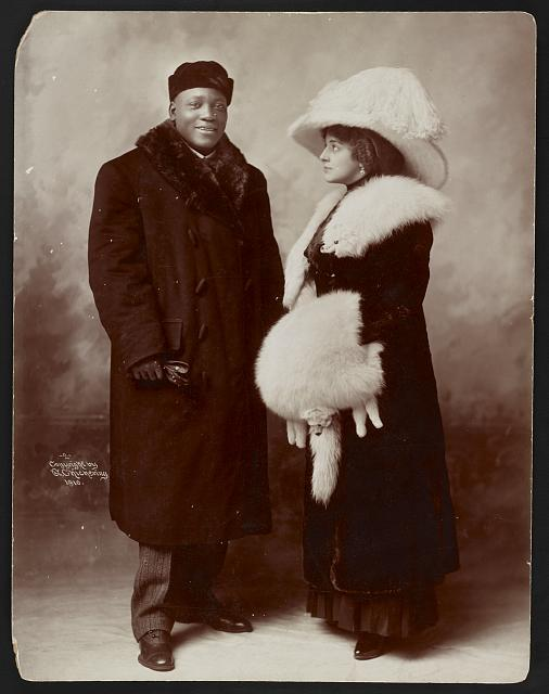 [Jack Johnson and his wife Etta, full-length portrait, standing, wearing winter coats]