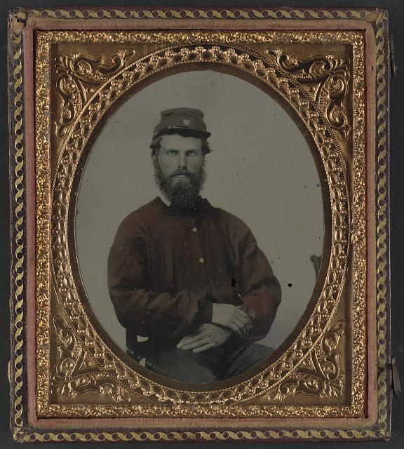 [Unidentified soldier in Confederate uniform with red shirt and kepi]