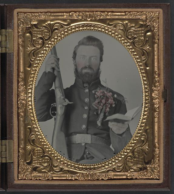 [Private David Lowry, of Company E, 25th Virginia Cavalry Regiment, Company A, 41st Virginia Infantry Regiment, and Company D, 47th Virginia Infantry Regiment, in uniform and corsage of flowers with musket and book]