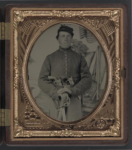 [Unidentified soldier in Union uniform with two Colt revolvers and cavalry sword in front of painted backdrop showing encampment]