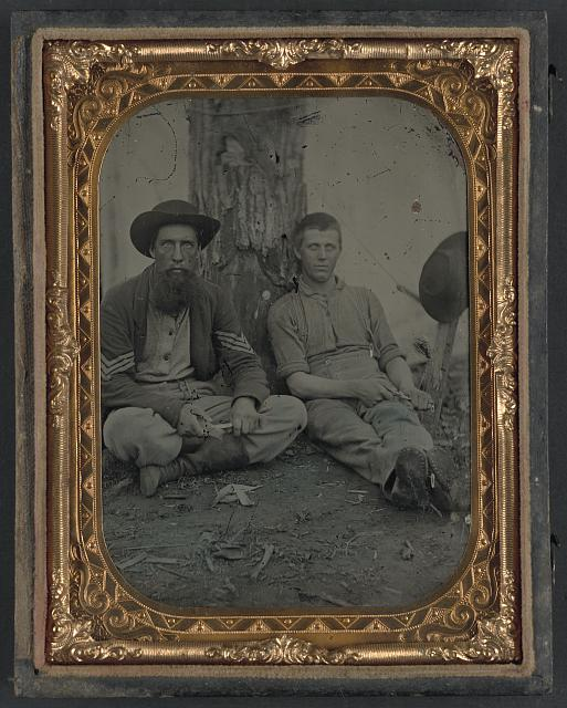 [Unidentified soldier in Union uniform and unidentified young man sitting on the ground and whittling]