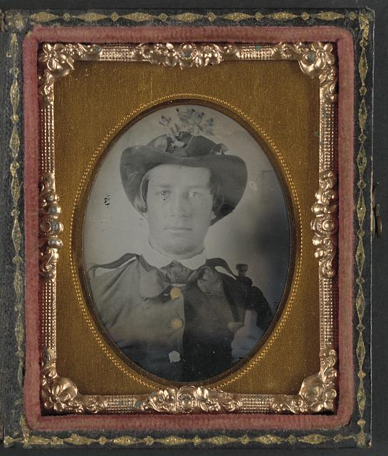 [Private Thomas Bobo of H Company, 5th South Carolina Infantry Regiment; H Company, 9th South Carolina Infantry Regiment;  K Company,1st South Carolina Light Artillery Regiment in uniform and hat decorated with flowers]