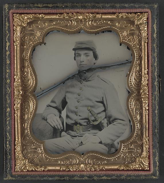 [Unidentified soldier in Confederate uniform with early model two-piece Confederate belt buckle and North Carolina manufactured sword]