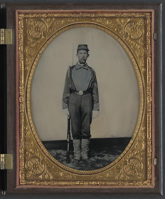 [Corporal Samuel H. Overton of A Company, 44th Virginia Infantry Regiment and A Company, 20th Battalion Virginia Heavy Artillery Regiment in uniform and kepi with bayoneted musket]