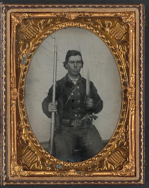 [Unidentified soldier in Confederate uniform with D-guard Bowie knife, musket, and revolver]