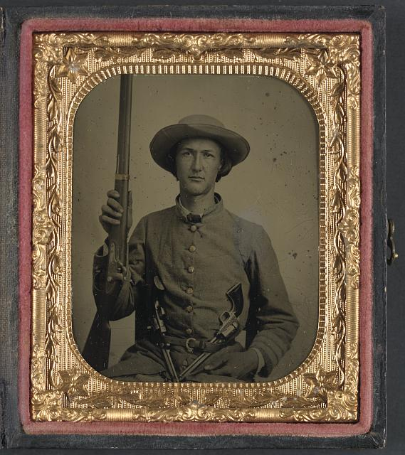 [Unidentified soldier in Confederate infantry uniform with model 1842 musket and two Colt revolvers]