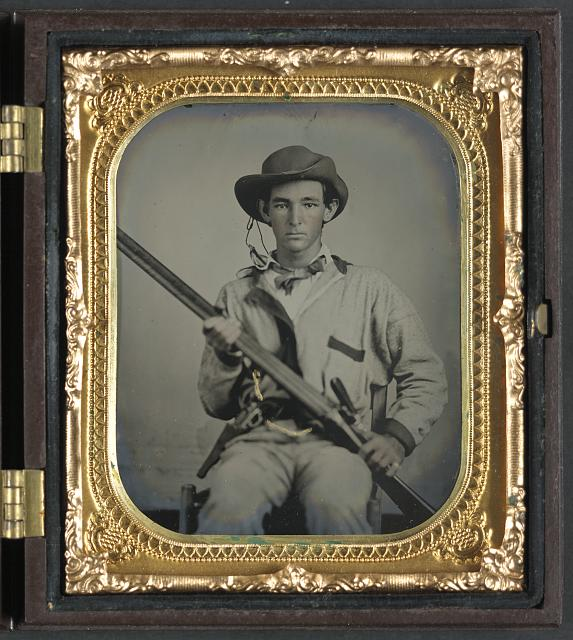 [Unidentified soldier in Confederate pullover hunting-style shirt with dark military-type trim with double barrel shotgun, revolver, and side knife]
