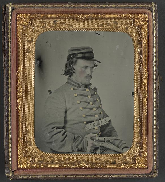 "[Unidentified corporal in Confederate uniform of Company K, ""Jake Thompson Guards,"" 19th Mississippi Infantry Regiment, with revolver]"