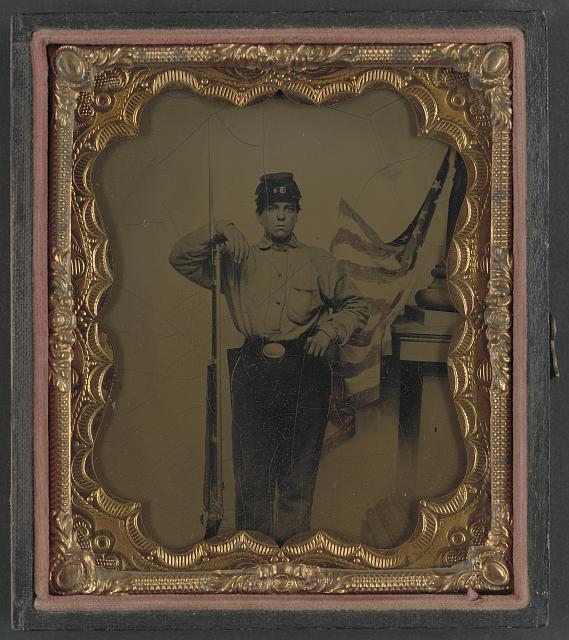 [Unidentified soldier in Union uniform with bayoneted musket in front of painted backdrop showing American flag and column pedestal]