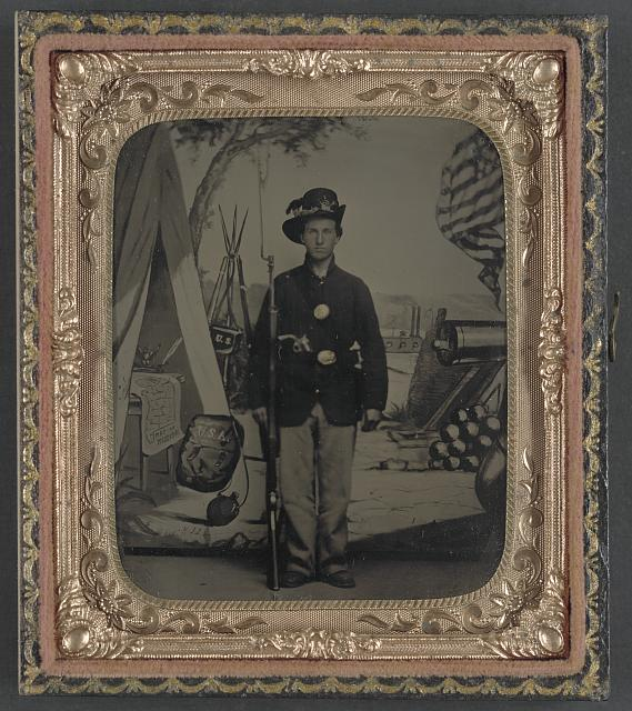 [Unidentified soldier of 33rd Missouri Infantry Regiment with bayoneted musket and revolver in front of painted backdrop showing weapons and American flag at Benton Barracks, Saint Louis, Missouri]