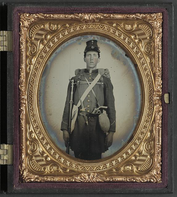 [Unidentified soldier in Union uniform with bayoneted musket, knife, revolver, canteen, and knapsack]