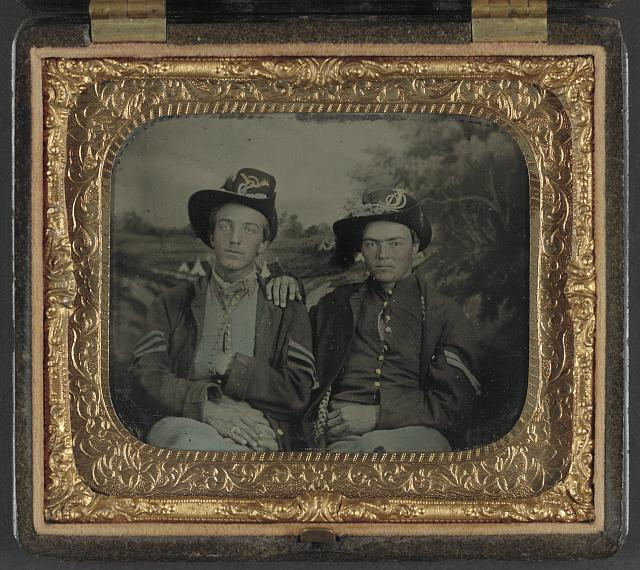 [Unidentified sergeant and corporal in Union uniforms in front of painted backdrop showing camp scene]