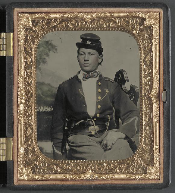 [Unidentified soldier of the 26th New York Infantry Regiment with revolver in front of painted backdrop showing camp scene]