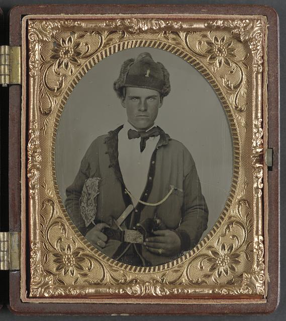 [Unidentified solder in Union uniform, U.S. cavalry belt, and fur hat bearing number 1, with Bowie knife and revolver]