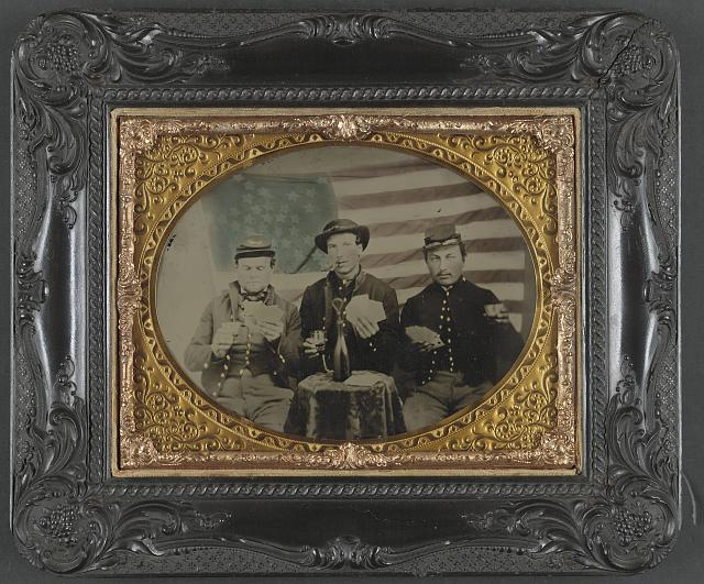 [Three unidentified soldiers playing cards, smoking, and drinking in front of American flag]