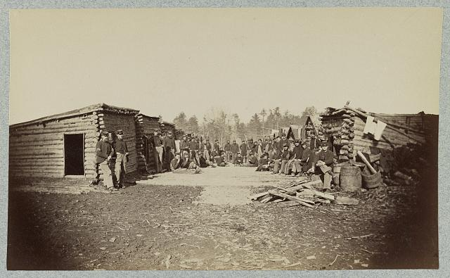 [Union soldiers, in camp, posed in front of log buildings]