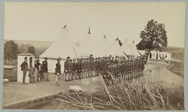[Union soldiers lined up in two rows in front of tents]