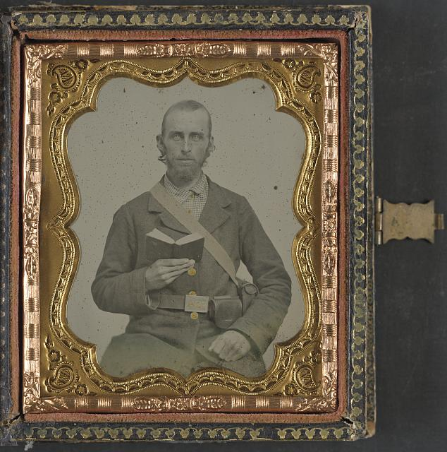 [Unidentified soldier in Confederate uniform and C.S.A. belt buckle with cartridge box and percussion cap box, holding a book]