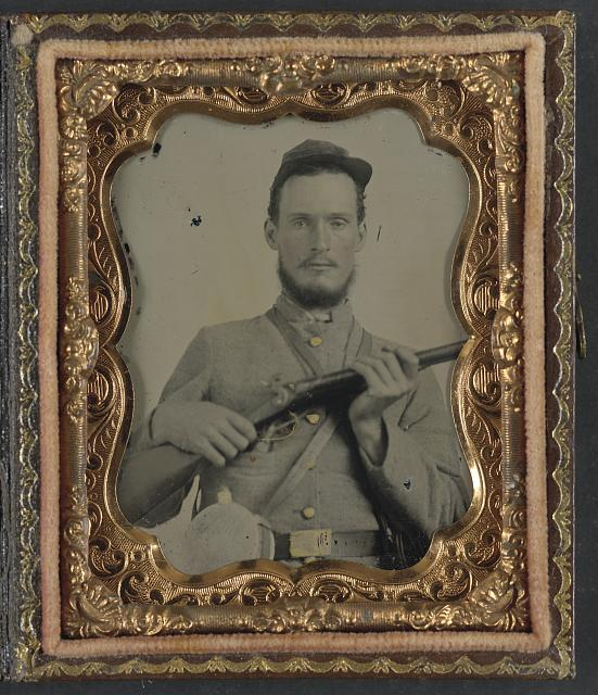 [Unidentified soldier in Confederate uniform with percussion shotgun and two canteens]