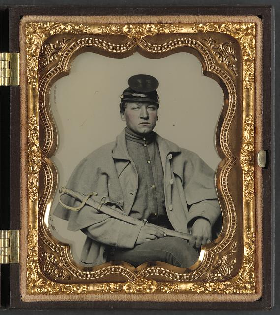 [Unidentified soldier in Confederate artilleryman uniform and greatcoat with sword]
