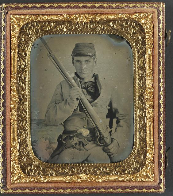 [Unidentified soldier in Confederate infantry uniform with musket and brass framed revolver]