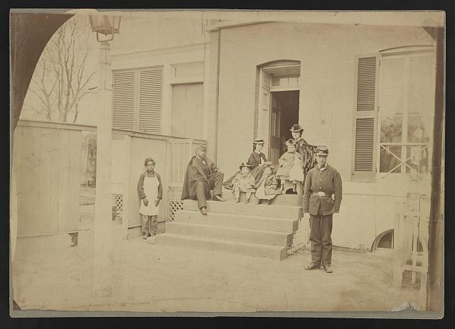 [Two unidentified soldiers and others at the front steps of a house]