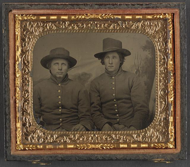 [Two unidentified soldiers in Union privates' uniforms in front of painted backdrop]