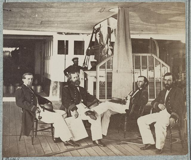 [Four Navy officers seated on board a ship]
