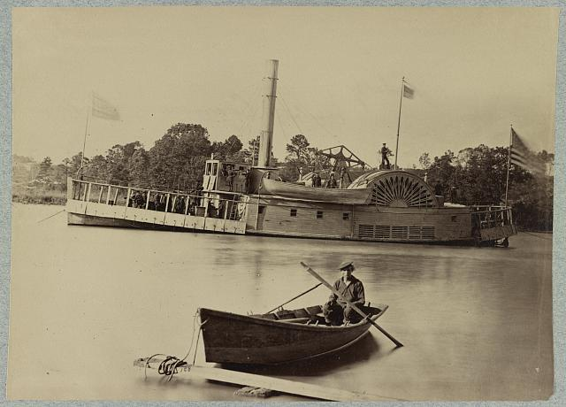 [A sailor sits in a small boat in the foreground with a side wheeler in the rear]