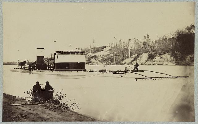"Monitor in Trent's Reach, James River, Va. showing torpedo finder at bow. Butlers ""Crow's Nest"" and battery on bank of river"