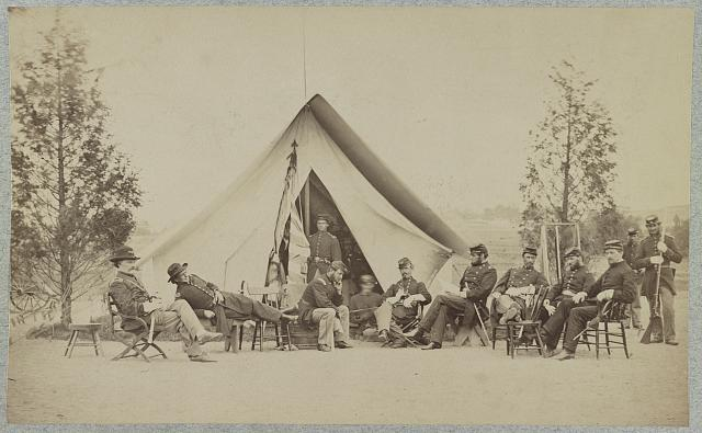 [Group of soldiers relax in front of a tent]