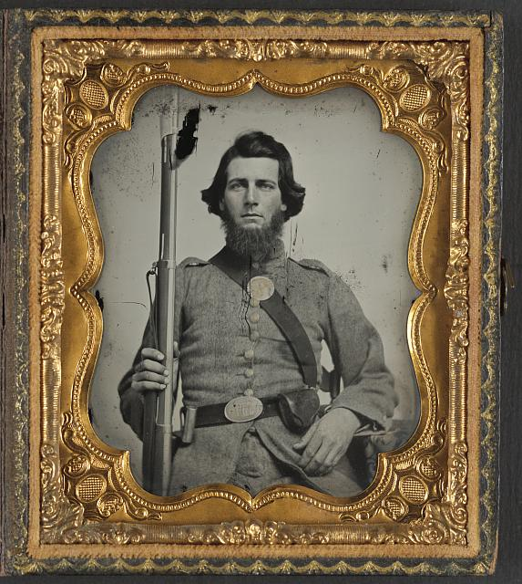 [Unidentified soldier in Confederate uniform and Georgia state seal belt buckle with musket]