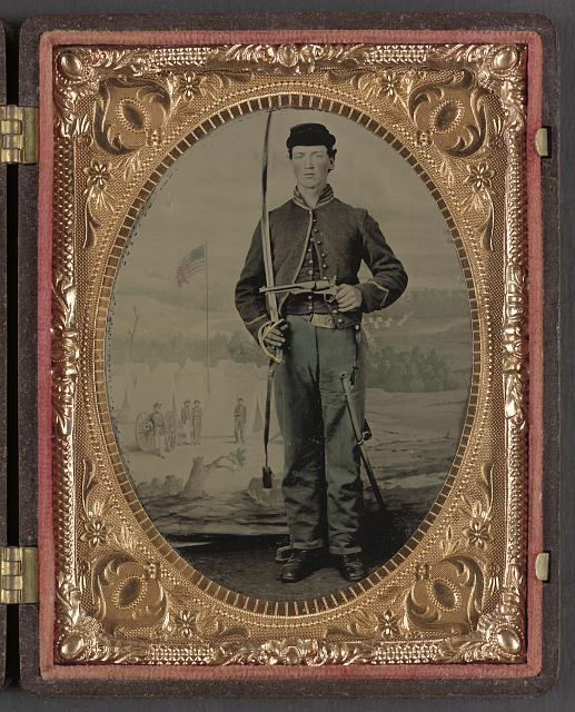 [Unidentified soldier in Union cavalry uniform with sword and pistol in front of painted backdrop tree stump and military camp]