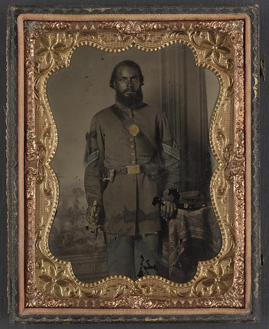 [Unidentified African American soldier in Union infantry sergeant's uniform and black mourning ribbon with bayonet in front of painted backdrop]