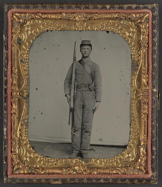 [Unidentified soldier in Confederate uniform and snake belt buckle with Enfield rifle and saber bayonet]