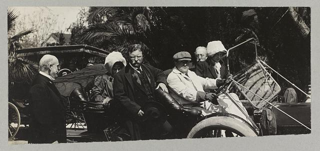 [Theodore Roosevelt and others disembarking from an open automobile]