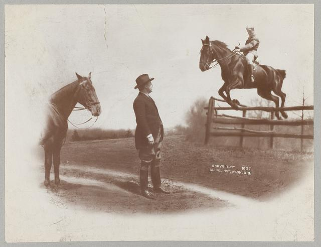 [Theodore Roosevelt watching his son Theodore Jr., who is riding on horse jumping over fence]