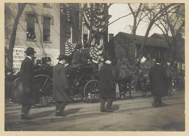 [Theodore Roosevelt and 2 other men in horse-drawn carriage, men walking along side, during inauguration day]