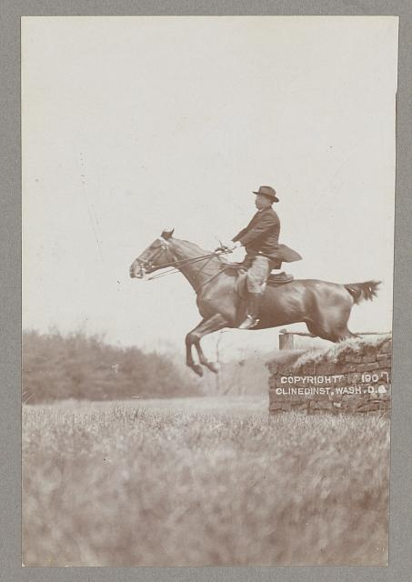 [Theodore Roosevelt, side view, on horseback jumping over stone wall]