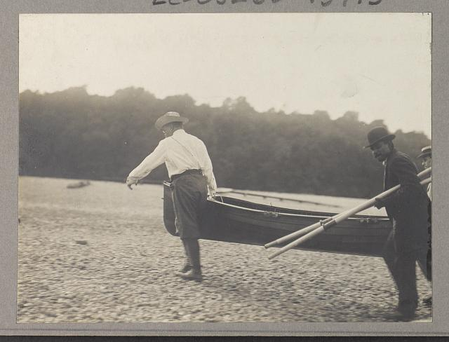 [Theodore Roosevelt and another man carrying a canoe as a third man carries the oars]
