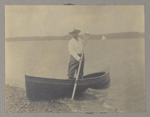 [Theodore Roosevelt, standing up in canoe, pushing away from shore with oar]